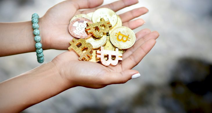 Two hands holding physical coins representing cryptocurrency